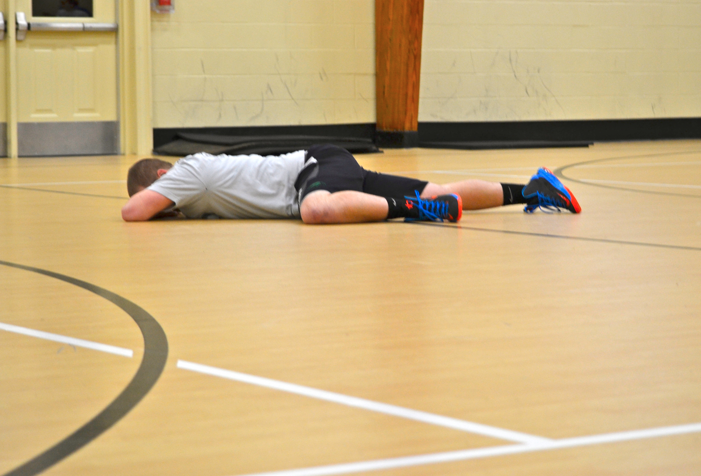 WPU student lying face down on the gym floor.