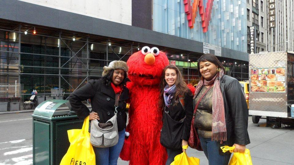 Students returning from shopping taking a picture with a life-sized Elmo