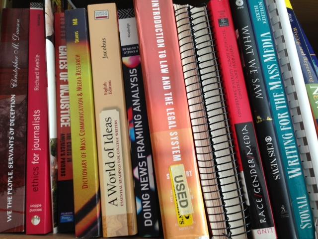 several textbooks sitting on the library shelf