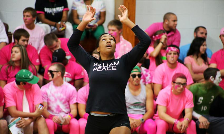 girl volleyball player dressed in all black with her hands up and eyes looking up towards the ball. Background of dozens of students sitting on the bleachers behind her dressed up in all pink.