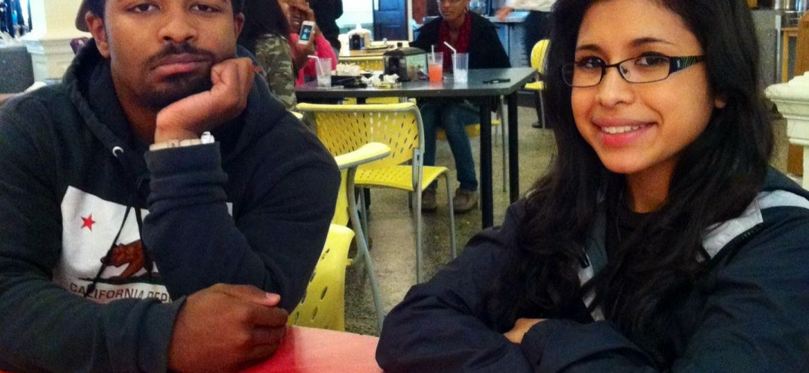 two students sitting in the school cafeteria, boy on the left frowning while having his chin is resting in his hands, girl on the left wearing glasses and smiling. people in the background sitting at a table eating food.