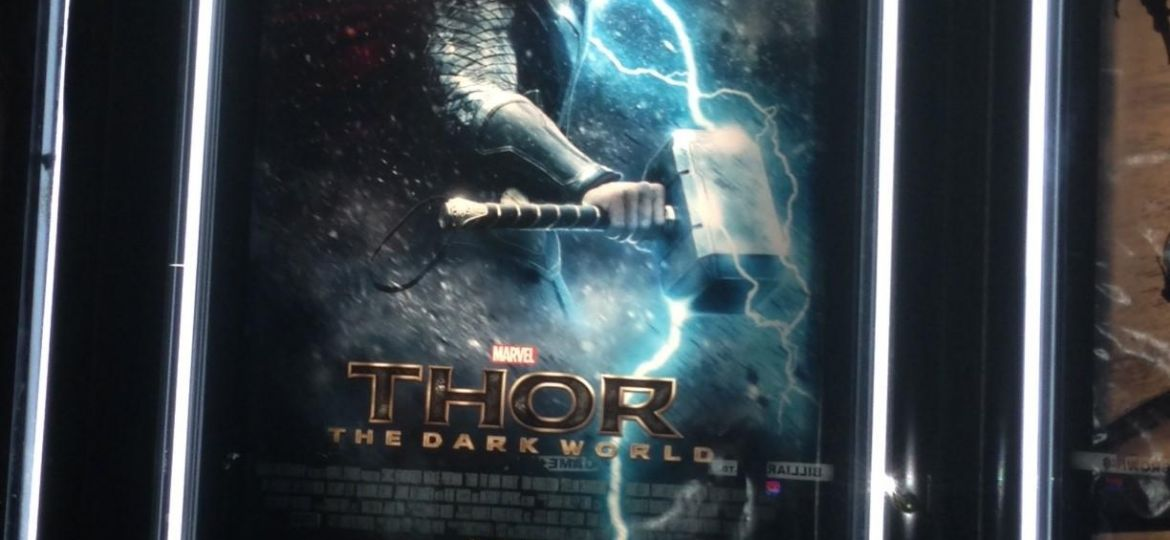 picture of the main character Thor holding his steel hammer in the rain with a bright lightening bolt behind him