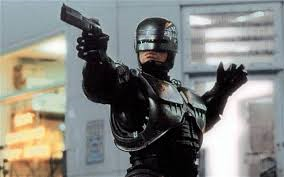 a man in a all black leather costume including a black helmet, holding a gun pointing in out away from his body.