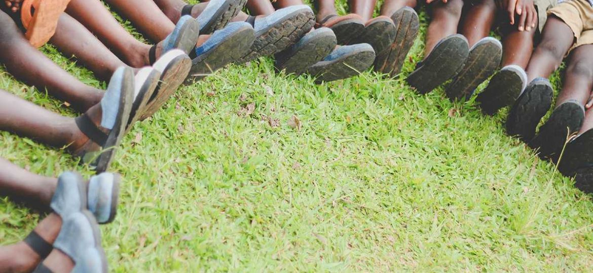 large group of Ugandan children sit with their feet in a circle on grass