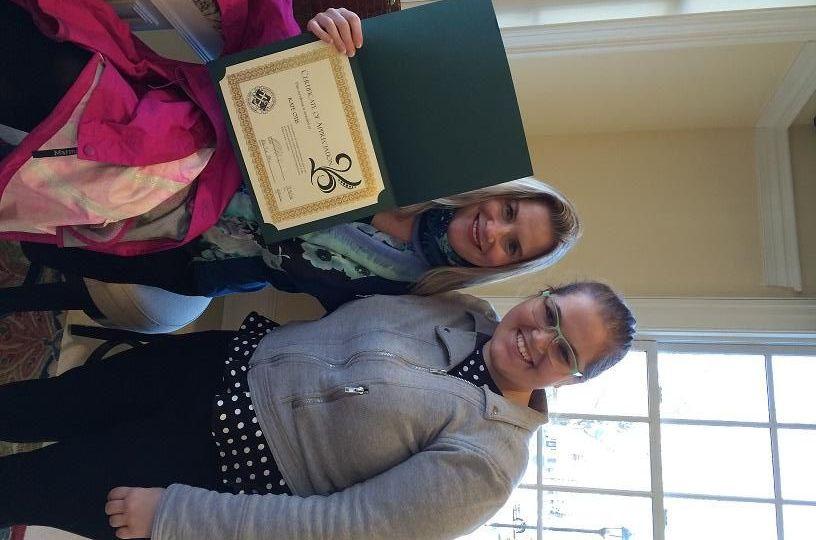 Katie Otis holds an award next to Rebekah Malkin
