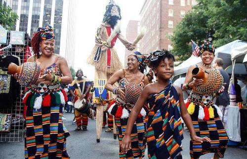 Women of color parade through downtown wearing African garments