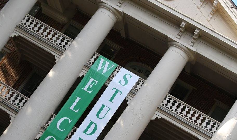 """Main Building with 2 green and white folders hanging inscribed """"WELCOME"""" and 'STUDENTS"""""""