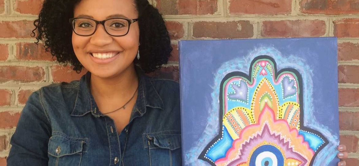 Female student Natalie Arthur stands holding her painting of a mandala