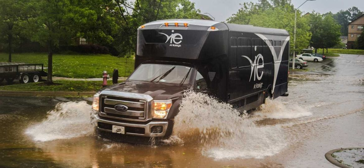 The Vie at Raleigh black Ford shuttle splashes through a large puddle at the Vie