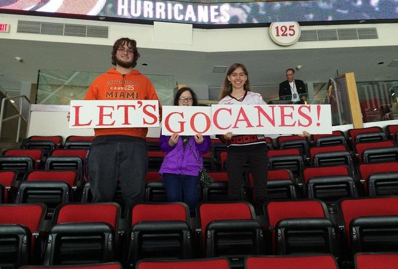 """3 Peace students stand in Section 125 of the PNC Arena holding a sign that reads """"LETS GO CANES"""""""