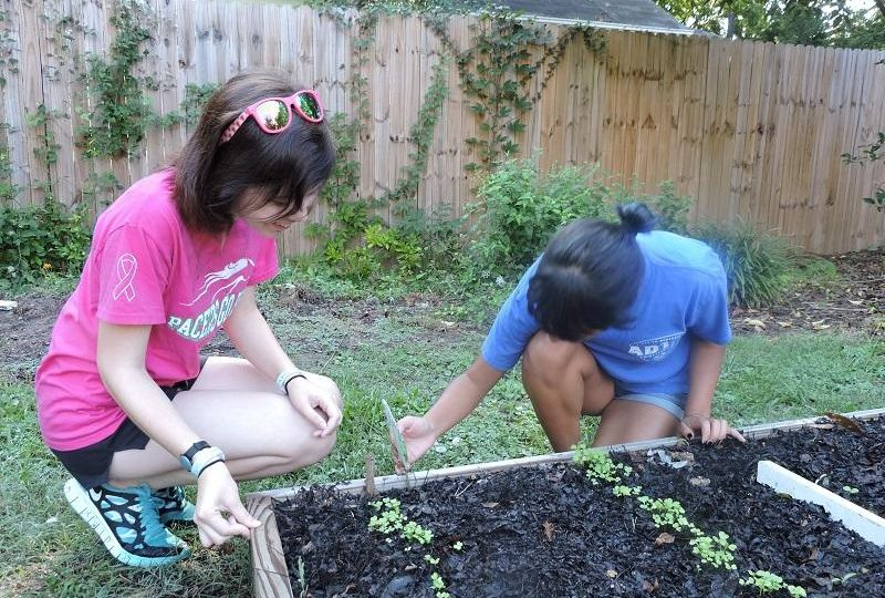 2 WPU female students crouch over a flowerbed