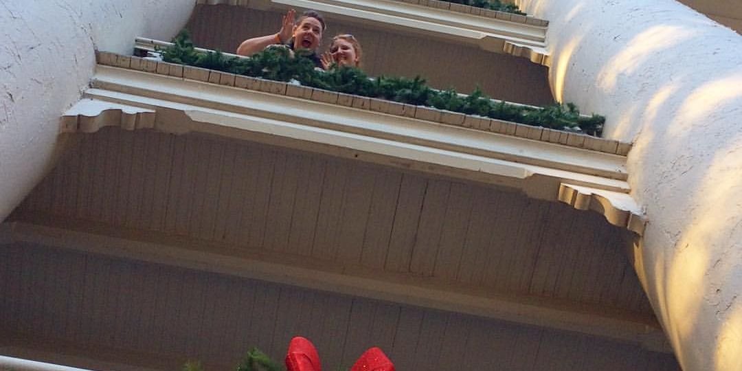 Two female students are seen from below on the 2nd floor of Main Building. 2 columns frame the photo with Christmas wreaths hanging from each floor
