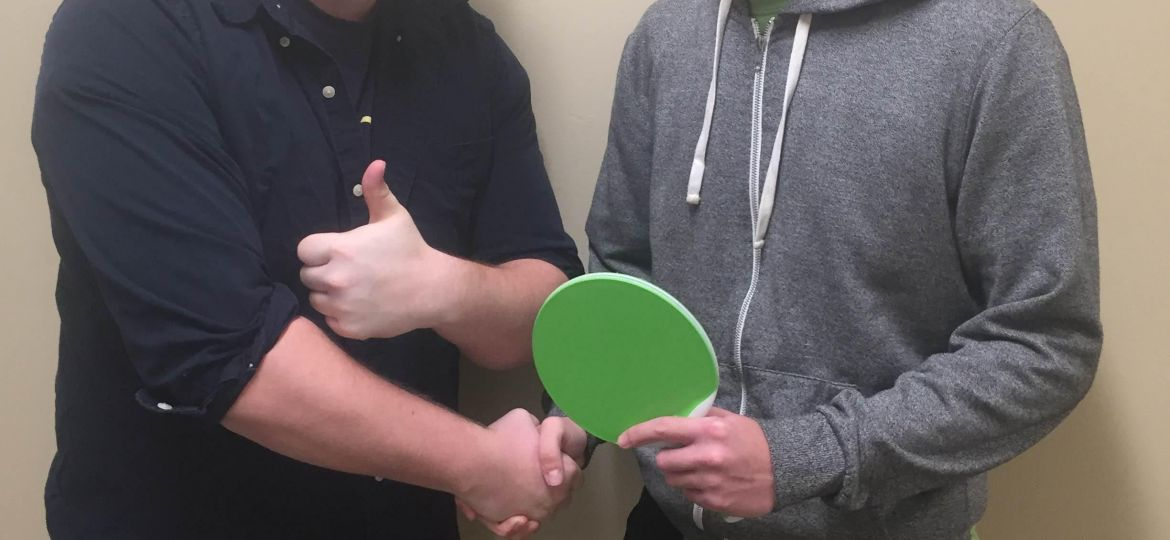 Student Caleb Lethbridge stands in a hat on the left shaking the hand of fellow student Patrick Ralph who holds a green ping pong paddle
