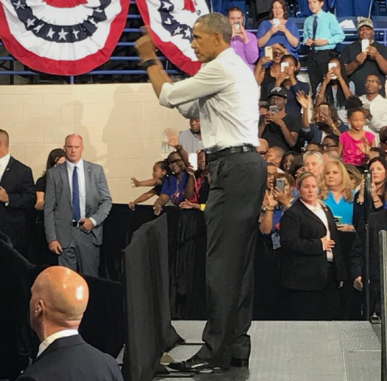 Former President Barack Obama stands in formal attire gesturing towards a crowd of people