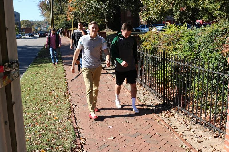 Front view of 2 WPU male athletes walking in high heels on the sidewalk outside of the school