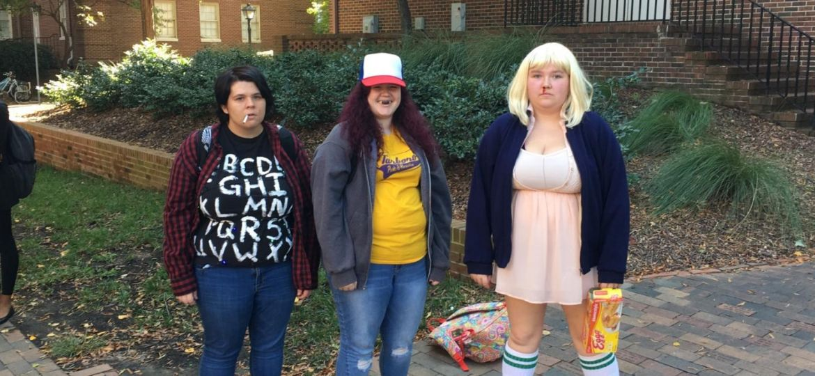 Three female students stand outside of Pressly Building dressed as characters from 'Stranger Things'