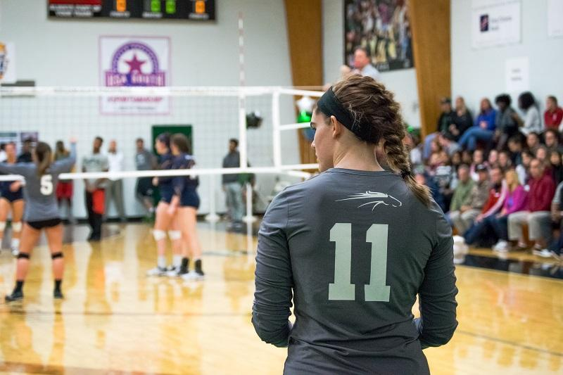 William Peace University volleyball player stands to the right of a volleyball game in the Peace gymnasium