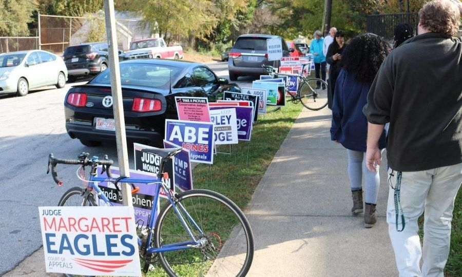 People walking along sidewalk lined with election signs