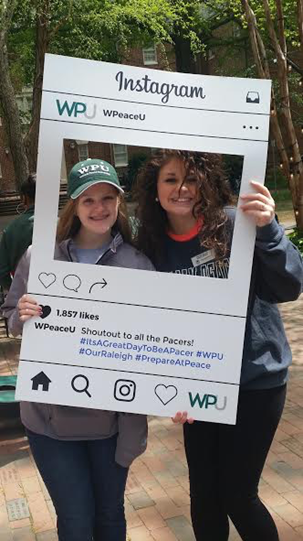 2 WPU students stand with Instagram board