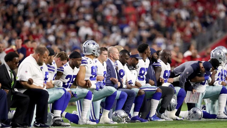 Football players kneeling in a line for National Anthem