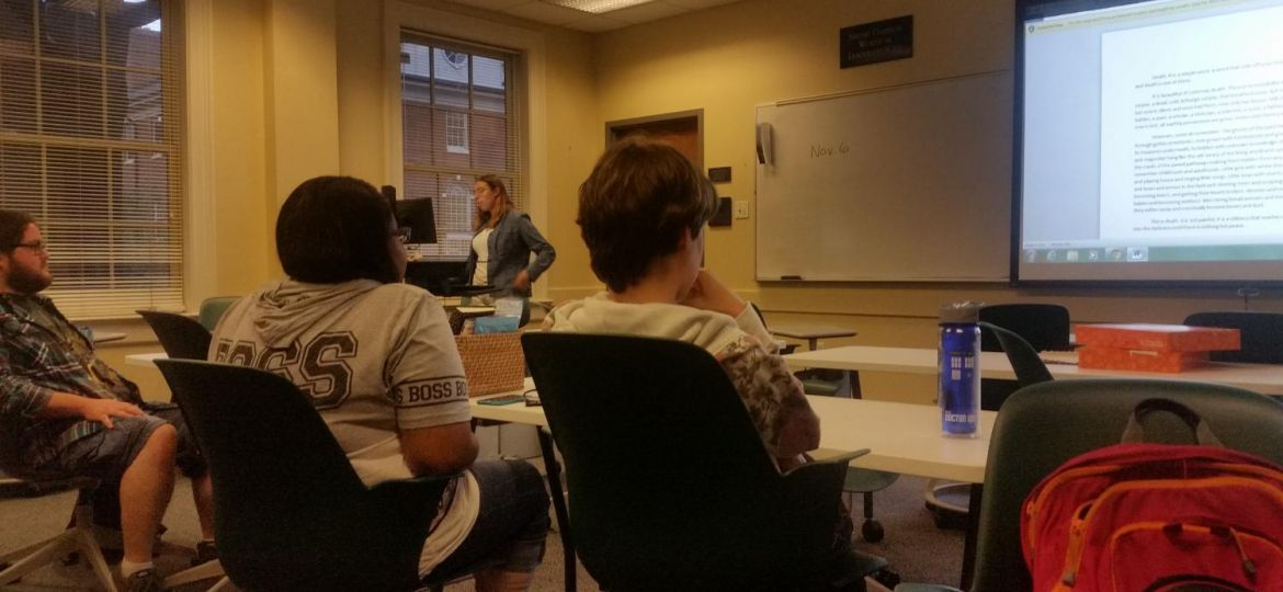Two students sitting in chairs looking at a white board.
