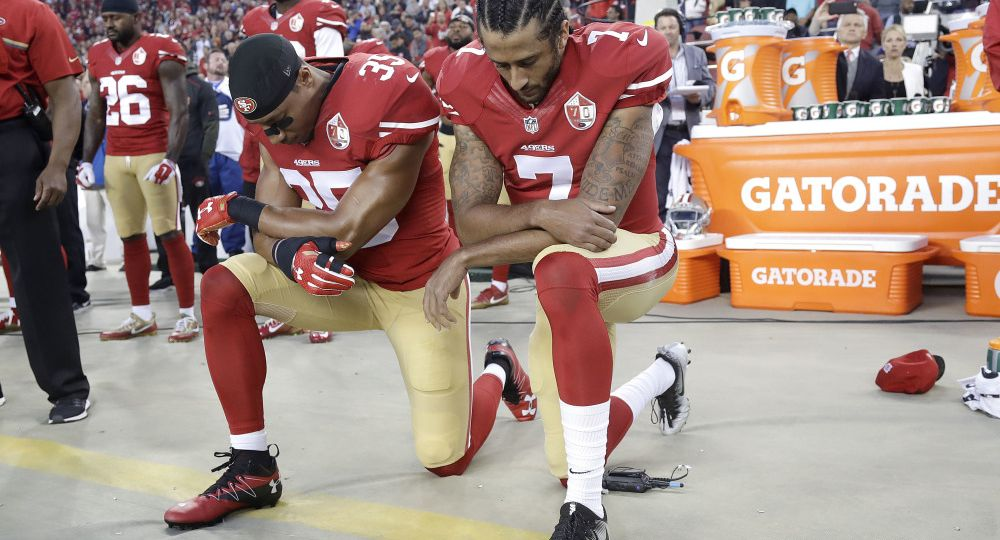 Two NFL players in red jerseys kneeling.