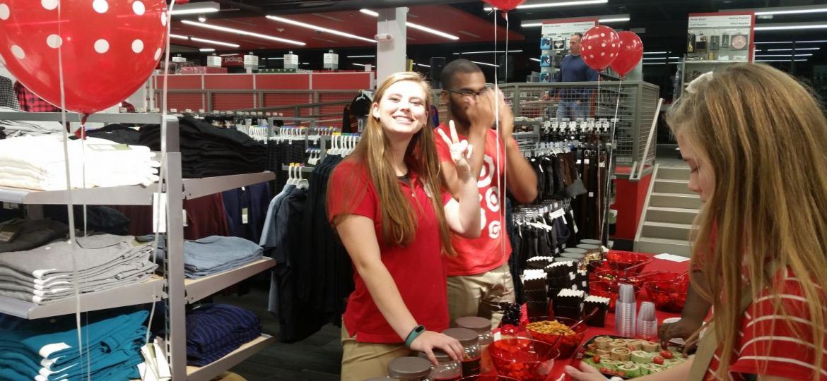 Target Employee wearing red shirt smiling as she is in an isle working.