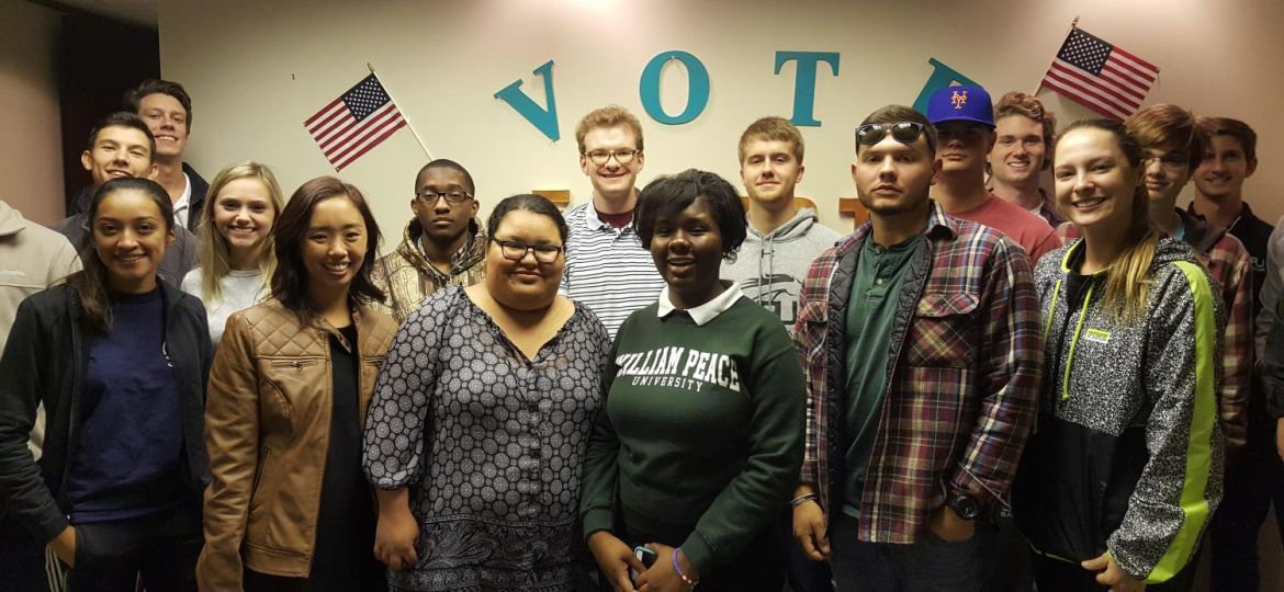 WPU class standing in front of wall that says vote.