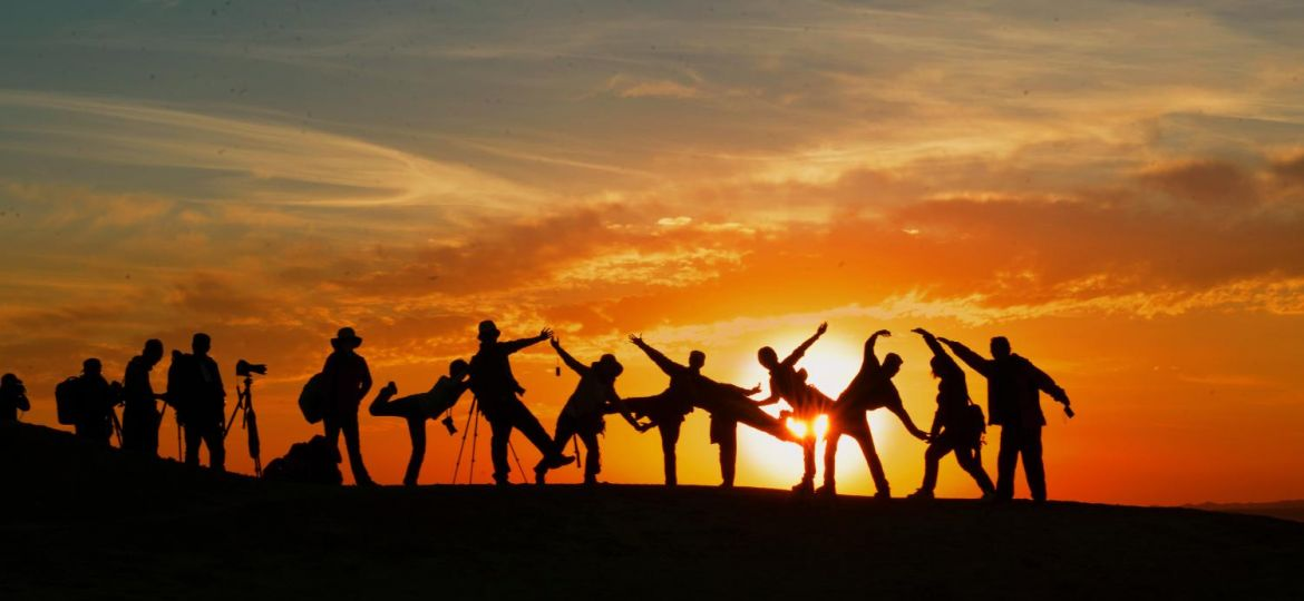 A group of friends posing while watching the sunset