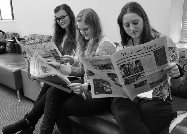 Peace Times Staff at conference reading newspapers