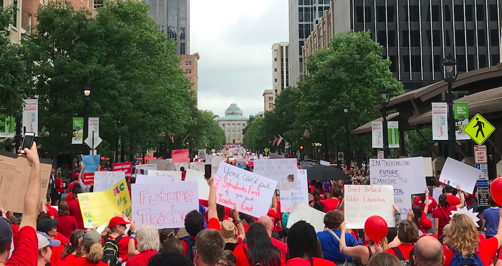 North Carolina teachers march up Fayetteville Street holding signs