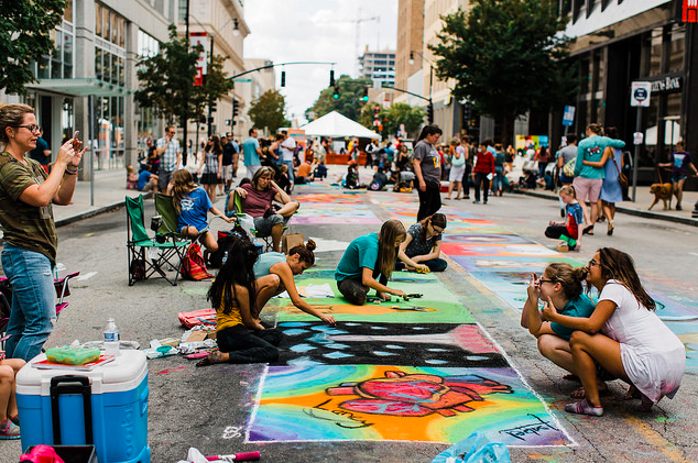 People Drawing with Chalk on Pavement