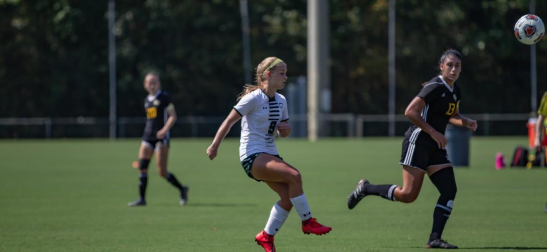 Freshman Raine Greene kicking the ball past her teams opponent