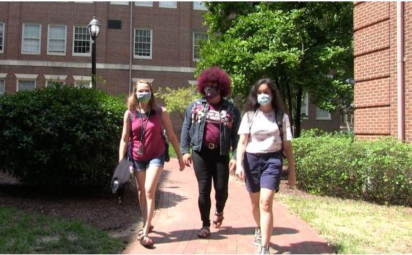 3 students in masks walk down sidewalk