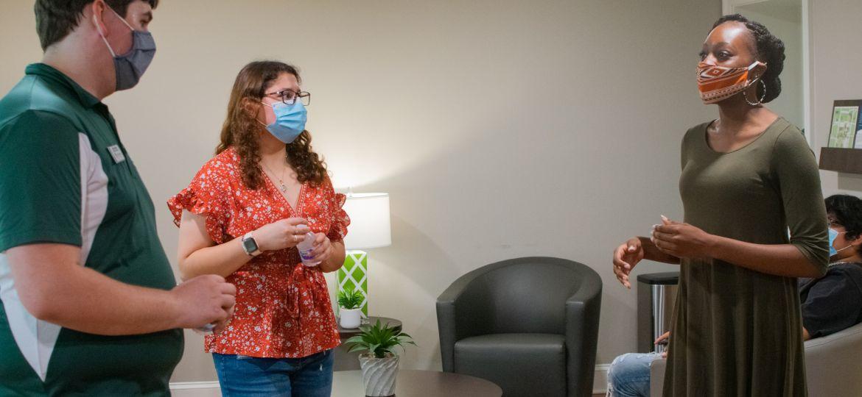 Three students with masks talk